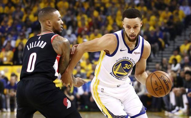 Stephen Curry dribla a Damian Lillard.